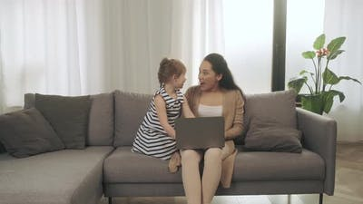 Happy Daughter and Mother Looking at Laptop on Couch