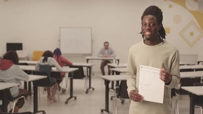 African Student Showing Paper on Camera