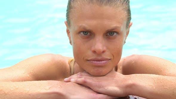 Thumbnail for Gesunde Frau ruht am Pool und Blick auf die Kamera