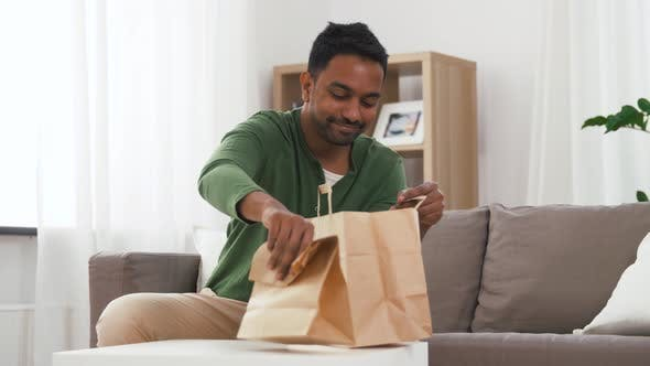 Cover Image for Smiling Indian Man Unpacking Takeaway Food at Home