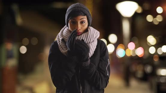 Thumbnail for Black woman wearing scarf and gloves, shivering on urban street on winter night