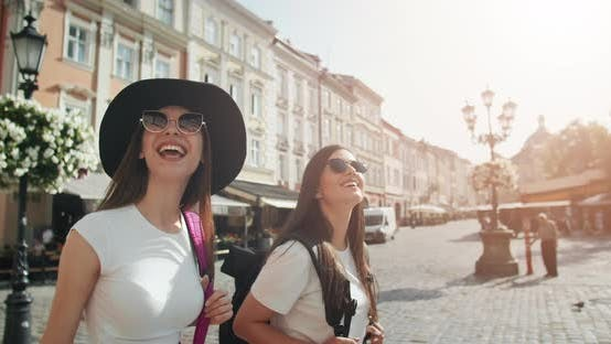 Cover Image for Female Tourists with Backpacks Walking in City