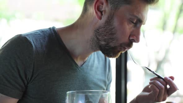 Man Eating Food And Drinking Beer At Restaurant