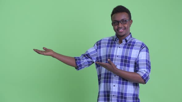 Thumbnail for Happy Young African Hipster Man Showing Something