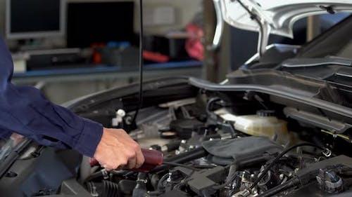 mechanic hand using Tachometer checking engine of a car