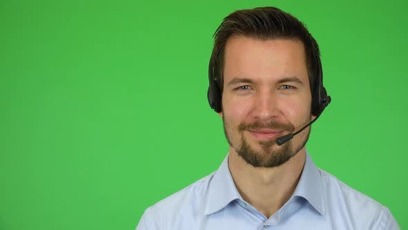 Thumbnail for A Young Handsome Call Center Agent Smiles at the Camera - Closeup - Green Screen Studio