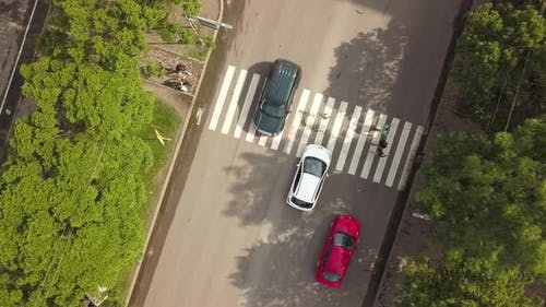 Aerial top down view of street with moving cars and zebra crosswalk with crossing pedestrians.