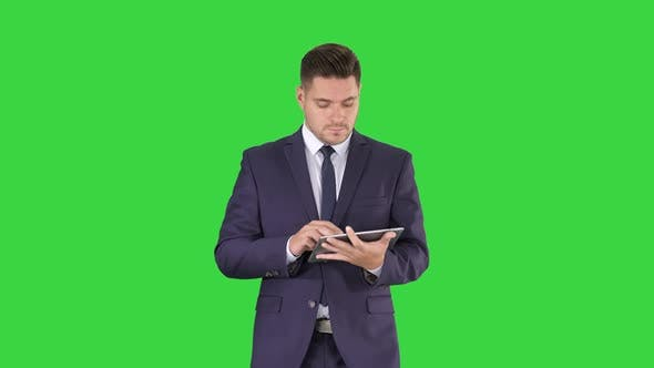 Thumbnail for Man in Suit Walking and Using Digital Tablet on a Green Screen