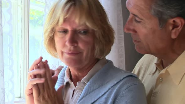 Cover Image for Closeup portrait of mature woman being consoled by husband looking out window