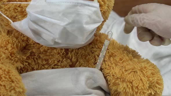 Thumbnail for A Teddy Bear Measures the Temperature with a Mercury Thermometer. The Doctor Takes the Thermometer