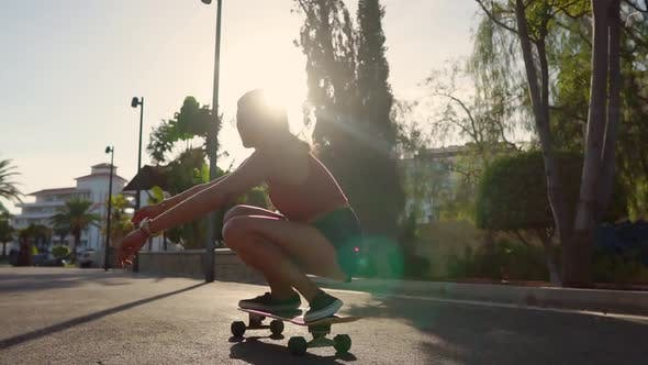 Thumbnail for A Young Woman in the Summer Riding a Longboard Near the Palm Trees in Shorts and Sneakers