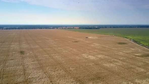 Thumbnail for Aerial View Gold Wheat Field and Operating Harvester