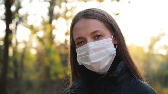 Thumbnail for Woman in Medical Safety Protective Face Mask Walking Outdoors in Park