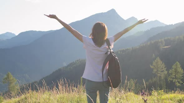 Woman with Raised Arms on Top of a Mountain