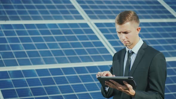 Cover Image for A Young Businessman Uses a Tablet Near a Solar Power Station