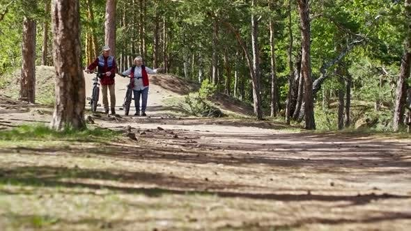 Thumbnail for Senior Couple with Bicycles Walking in Forest
