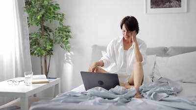 Woman in Bed Having Video Call