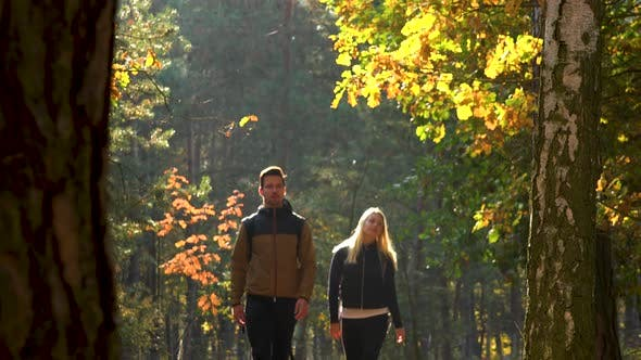 Thumbnail for A Hiking Couple Walks Through a Forest on a Sunny Day - Front View