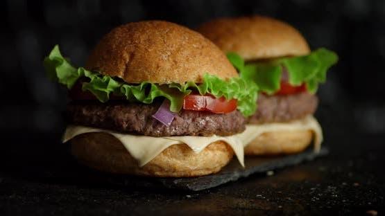Appetitliche Burgers auf einem Stone Board drehen sich.