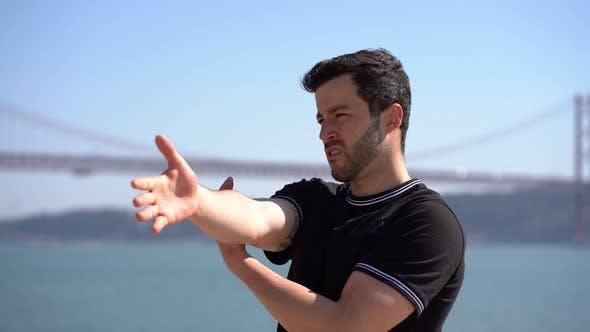 Thumbnail for Fokussierte junge Sportler Stretching Arme am Riverside