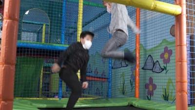 Children with face mask jumping on trampolines in the children's entertainment center.