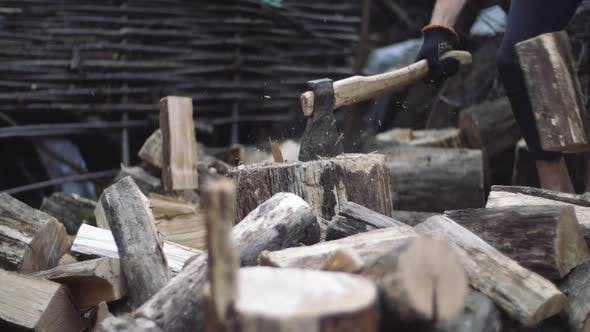 Man Chops Wood Outdoors in Slow Motion. Man's Hands Working with Ax. A Man Woodcutter Chops Tree