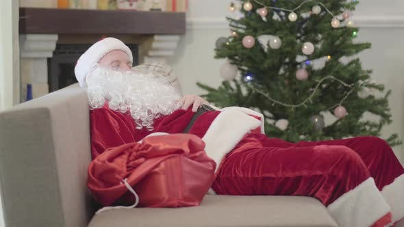 Thumbnail for Old Caucasian Man in Santa Claus Costume Sleeping on the Sofa at the Background of Xmas Tree