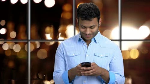 Young Smiling Man Typing Message on His Smartphone.
