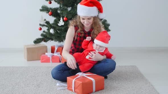 Thumbnail for Familienurlaub und Weihnachtskonzept. Junge Mutter mit einem Kind packe ein Weihnachtsgeschenk