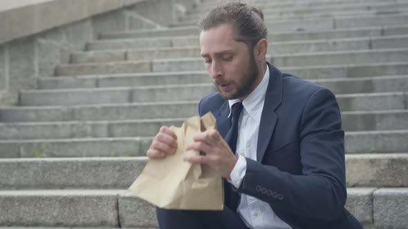 Thumbnail for Stressed Nervous Caucasian Man Breathing Into Paper Bag. Portrait of Depressed Businessman Sitting