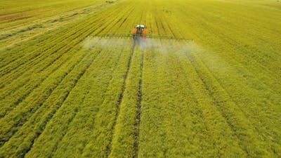 Tractor is Spraying Fertilizers Field