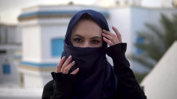 Thumbnail for Young Woman in Arabic Burqa, A Woman Looks at the Camera and Straightens a Scarf