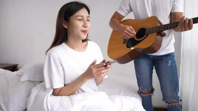 Happily couple playing guitar and sing a song at home