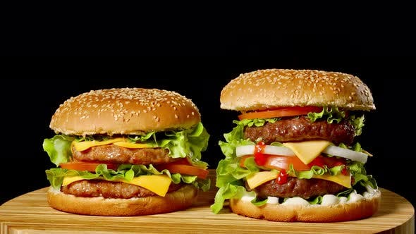 Thumbnail for Close-up of Two Appetizing Burgers with Sesame Buns Rotating on Black Background, of Fast Food