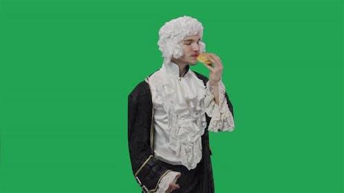 Portrait of Courtier Gentleman in Black Historical Vintage Suit and Wig Savoring Scent of