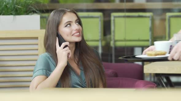 Gorgeous Woman Talking on Phone and Waiter Bringing Food and Drink