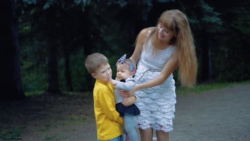 Young Mother and Her Two Sons Play with the Baby