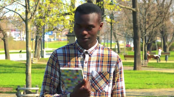 Thumbnail for A Young Black Man Holds a Book Against His Chest and Smiles at the Camera in a Park on a Sunny Day