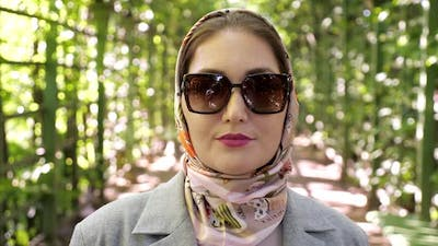 Closeup of a Woman in a Headscarf and Sunglasses Smiling in a Garden Arch