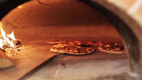 Peel Placing Pizza Baking in Oven at Pizzeria 4