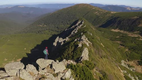 Aerial View of Hiker Woman with Backpack on Top of a Mountain