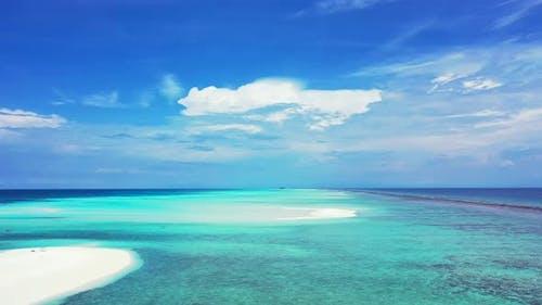 Beautiful drone travel shot of a sandy white paradise beach and aqua blue ocean background