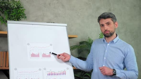Confident man teacher point marker diagram on flip chart online teaches students
