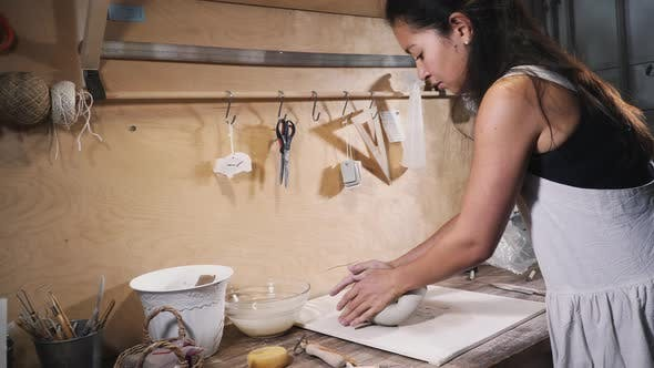 Thumbnail for Asian woman kneads clay in his studio