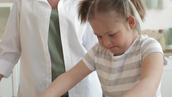 Thumbnail for Woman Watching Girl with Down Syndrome Kneading Dough