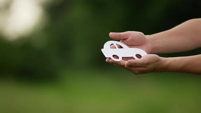People cupped hands showing paper car