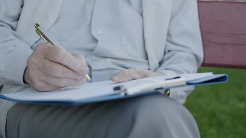 Close View of Old Male Hands Writing on Papers Lying on Knees on Park Bench