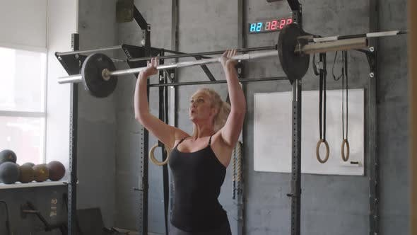 Woman Doing Barbell Overhead Squats in Gym