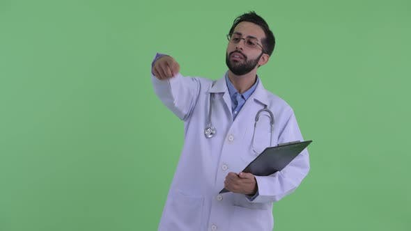 Thumbnail for Happy Young Bearded Persian Man Doctor Directing While Holding Clipboard