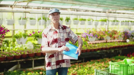Thumbnail for Researcher Examining Potted Plant At Greenhouse